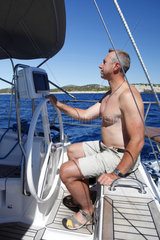 Segler am Steuer seiner Segelyacht in den Kornaten  Kornati Nationalpark  Kroatien