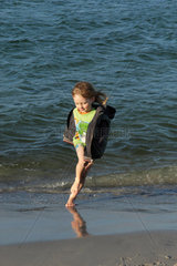 Ein kleiner Junge springt vor lauter Lebensfreude am Strand der Ostsee rum (model released)