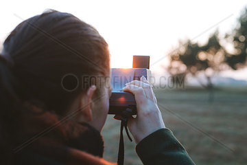 Junge Frau fotografiert mit Polaroid Kamera