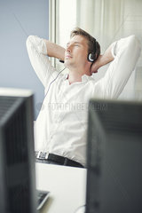 Man with arms behind head relaxing at work