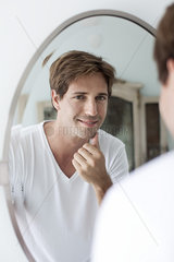 Man looking at self in mirror touching facial stubble