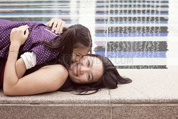 Mother and daughter lying together at edge of fountain  girl kissing woman's cheek
