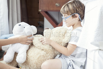 Little boy playing with teddy bear
