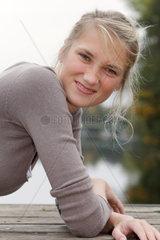 Blonde junge Frau  23 Jahre alt  relaxt auf einem Bootssteg und schaut keck in die Kamera.und zieht die Nase kraus (model released)