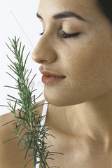 Young woman smelling spring of fresh rosemary  eyes closed