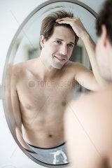 Man scrutinizing hairline in mirror