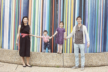 Family holding hands together in front of colorful striped sculpture  La Defense  Paris  France