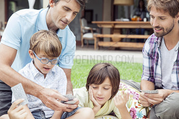 Same-sex couple playing card game with sons