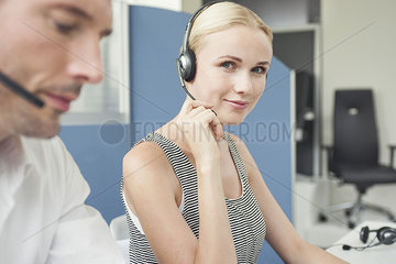 Woman wearing phone headset at desk