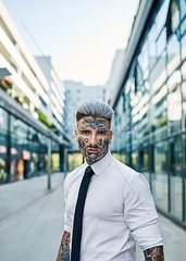 Young businessman with tattooed face walking in the city  portrait