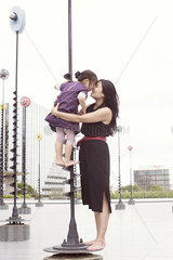 Mother and daughter nuzzling while standing on whimsical sculpture