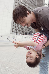 Father holding young son upside down  both laughing