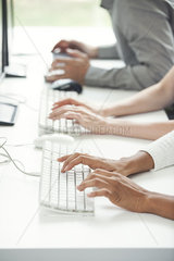 Office workers using computer keyboards