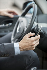 Businessman text messaging while driving  cropped