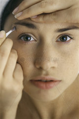 Young woman tweezing eyebrows  close-up