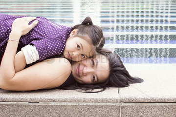 Mother and daughter lying together on edge of fountain  portrait