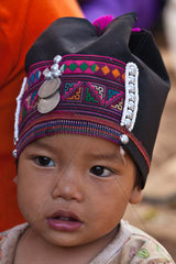 A baby girl of the AKHA tribe wears a childs headdresse made of beads  silver and hand loomed cotton  village near KENGTUNG or KYAINGTONG  MYANMAR