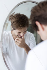 Man laughing to self  reflection in mirror
