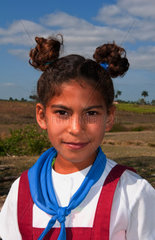 Girl student age 9 in uniform outside school in Habana Province in countryside outside city in Cuba