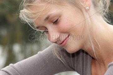 Blonde junge Frau  23 Jahre alt  schmunzelt und schaut vertraeumt zur Seite (model released)