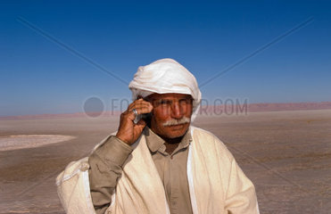 Arab man on cell phone Great Dry Salt Lake Chott el Jerid in Sahara Desert sand near Douz in Tunisia isolated Africa