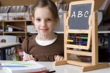 sechsjaehriges Maedchen im Klassensaal neben Schultafel