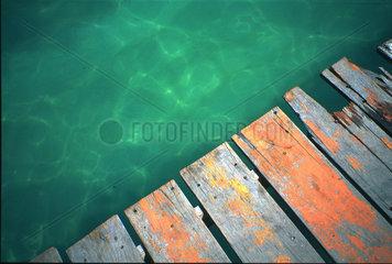 oranger Steg ueber gruenem Wasser