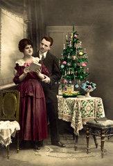 Paar unterm Weinachtsbaum mit Buch  ca. 1910