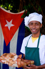 Chef cooking pig in square in Cienfuegos Cuba with Cuban flag