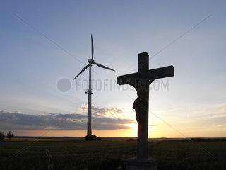 Windrad im Abendlicht mit Kreuz  Sueddeutschland