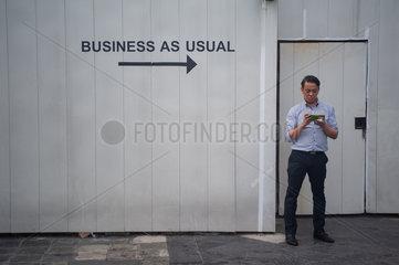 Singapur  Republik Singapur  Mann macht eine Arbeitspause in Raffles City