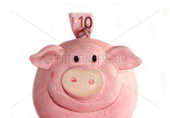 Zehn Euroschein steckt in dickem Sparschwein