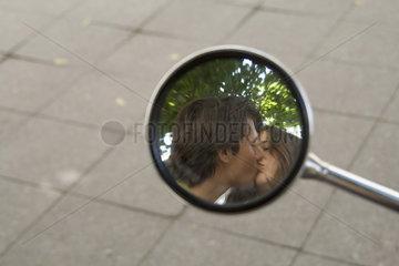 kuessendes Paar im Seitenspiegel eines Mototrrades