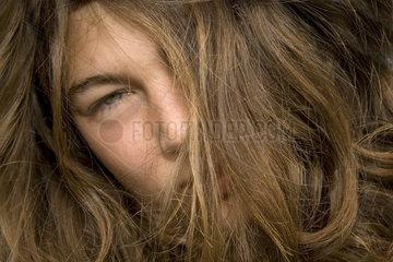 Jugendliche mit Haaren ueber Gesicht