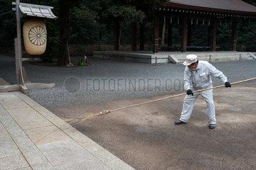 Tokio  Japan  Arbeiter fegt das Gelaende am Meiji-Schrein in Shibuya