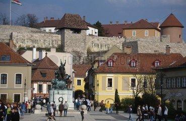 Fussgaenger in Stadtzentrum mit Stadtmauer
