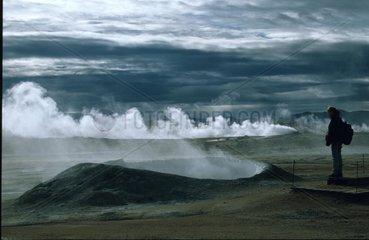 Frau steht vor dampfendem Geysir