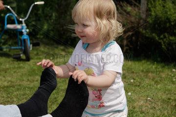 kleine Maedchen  2 Jahre alt  zieht an den Socken der Mutter (model released)