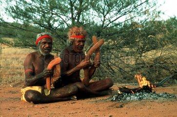 Aborigines mit Bumerang sitzen am Feuer