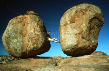 Frau zwischen zwei grossen runden Steinen