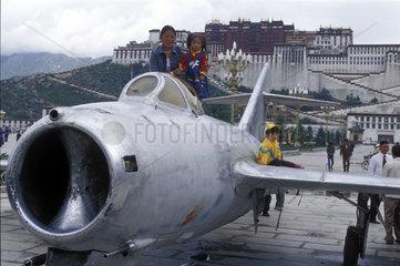 Kinder posieren auf Kampfjet vor dem Potala Palast