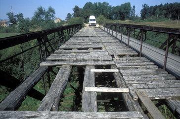 Transporter steht vor verfallener Holzbruecke