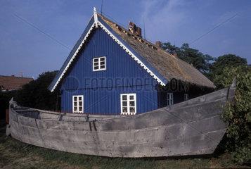grosses Ruderboot vor blauem Holzhaus