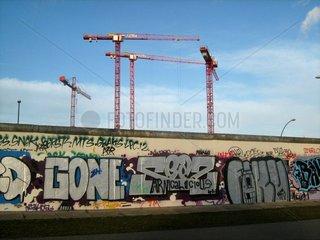 Baukraene an einem Rest der Berliner Mauer