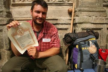 Pilger zeigt stolz ein Zertifikat - Camino de Santiago