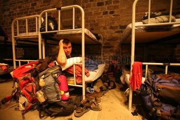 Pilger mit Schlafsack im Doppelstockbett in Herberge