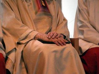Katholischer Pfarrer bei einer Messe zwischen Ministranten