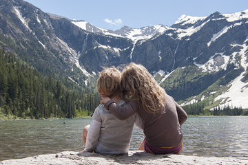 Young siblings enjoying view of mountains in Glacier National Park  Montana  USA