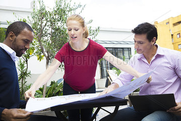 Businesswoman showing colleagues blueprint