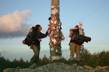 Pilger begutachten Pfahl mit Andenken Jakobsweg - Camino de Santiago